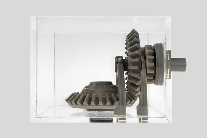 Gray 3D printed gears in a transparent cube by Zortrax
