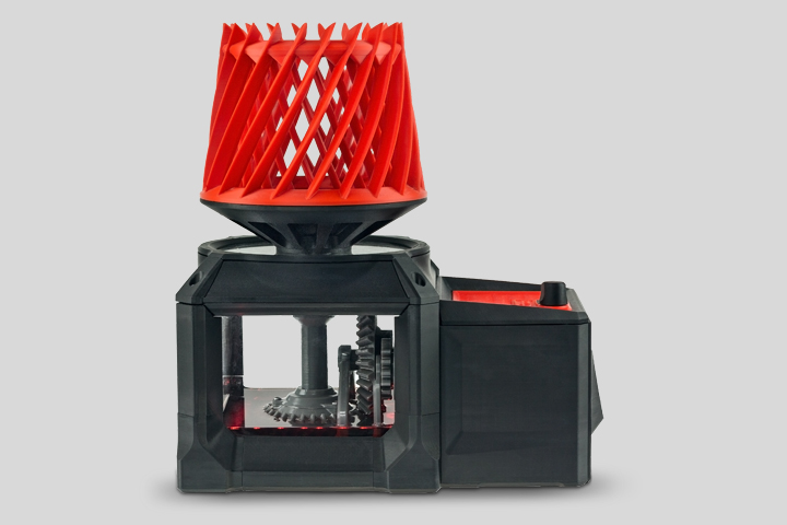 3D printed plastic device with gear and orange helix by Zortrax