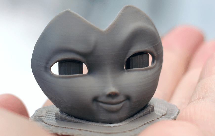 Small 3D printed mask lying on hand