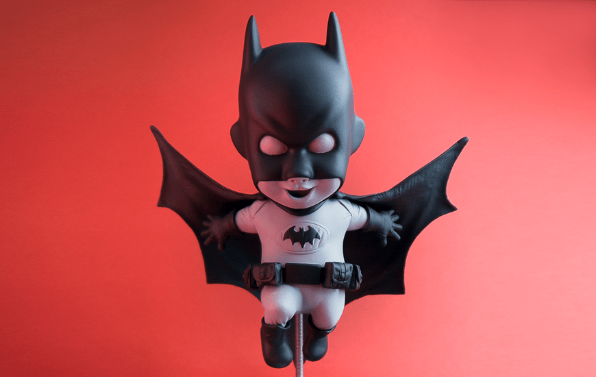 Black batman toy on red background