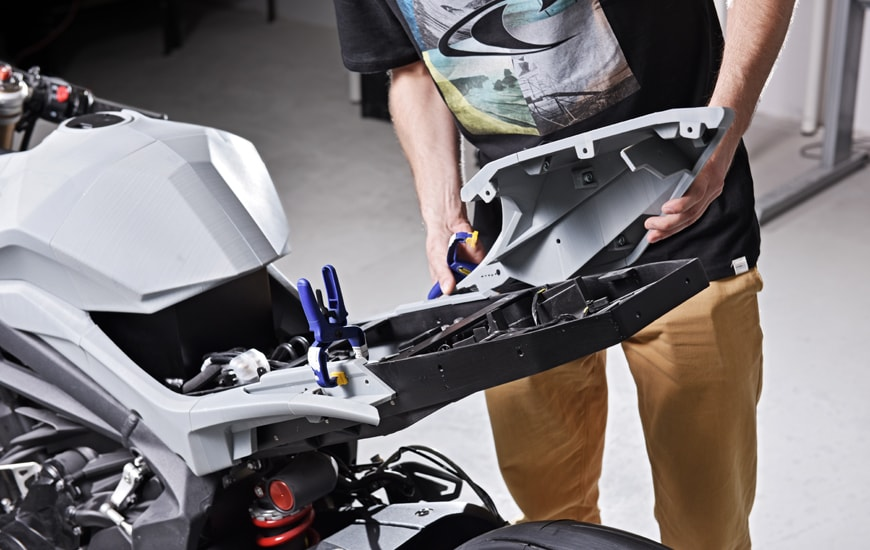 A man working with the silver 3D motorcycle