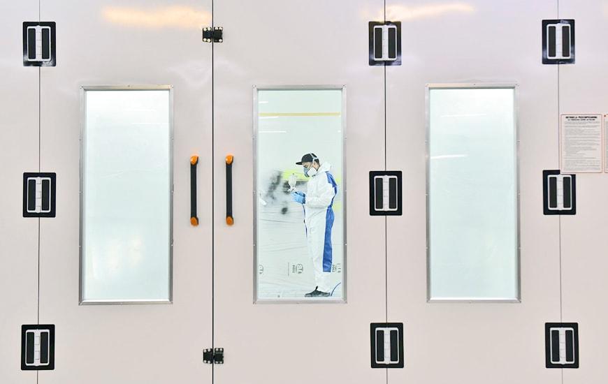 A man wearing safety uniform working behind white doors