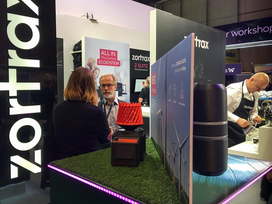 Man and woman talking each other at Zortax's stand