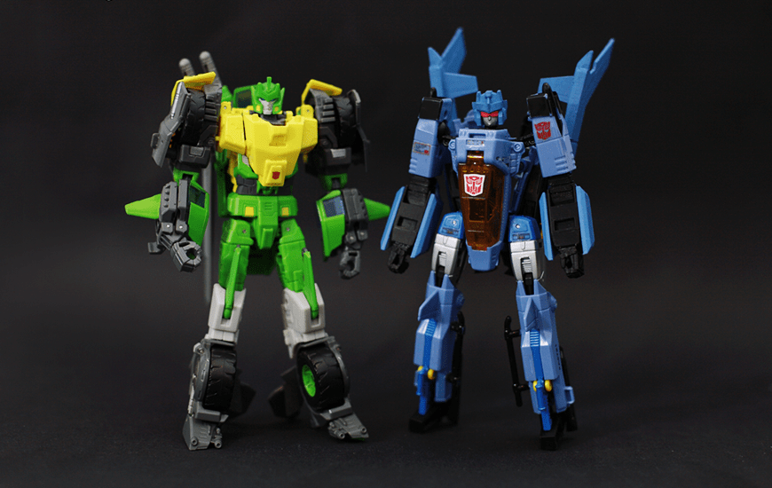 Two plastic 3D toy robots standing on black background
